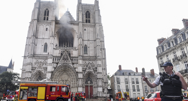 A French Police officer gestures as firefighters are at work to put out a fire at the Saint-Pierre-et-Saint-Paul cathedral in Nantes, western France, on July 18, 2020. Sebastien SALOM-GOMIS / AFP