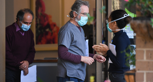 People wearing face masks are seen at the entrance of the Menarock Life aged care facility, where a cluster of some 28 new infections had been reported, in the Melbourne suburb of Essendon on July 14, 2020, as the city battles fresh outbreaks of the COVID-19 coronavirus.  William WEST / AFP
