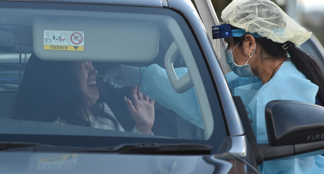 A medical worker (R) tests a woman in her car at a COVID-19 coronavirus testing station at the Crossroads Hotel, a popular drinking spot where at least 21 infections had been linked to a cluster there, in Sydney on July 13, 2020. PETER PARKS / AFP