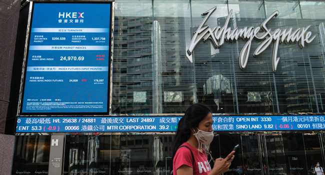 A woman wearing a face mask walks past a stocks display board outside Exchange Square in Hong Kong on July 16, 2020, as the city experiences another spike in COVID-19 coronavirus cases. Anthony WALLACE / AFP