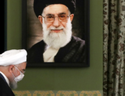 A handout picture provided by the Iranian Presidency on July 18, 2020, shows President Hassan Rouhani walking past a portrait of Iran's Supreme Leader Ayatollah Ali Khamenei. Iranian Presidency / AFP
