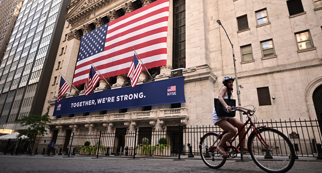 A woman rides past the New York Stock Exchange (NYSE) on July 13, 2020 at Wall Street in New York City. Johannes EISELE / AFP