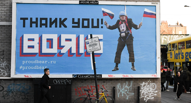 "In this file photo taken on November 08, 2018 A Brexit-themed billboard depicting Britain's former foreign secretary Boris Johnson waving Russian national flags reading ""Thank you Boris"" is seen in east London on November 8, 2018. Daniel SORABJI / AFP"