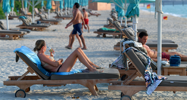 Tourists sunbathe at the beach of the Al Naseem hotel in the Gulf emirate of Dubai in the United Arab Emirates, on July 7, 2020. KARIM SAHIB / AFP