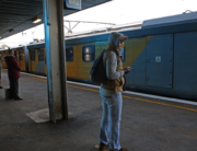 Commuters wearing face masks wait on a platform to board a train at Pretoria Station as the Passenger Rail Agency of South Africa (PRASA) resumes its operations on July 1, 2020. Phill Magakoe / AFP