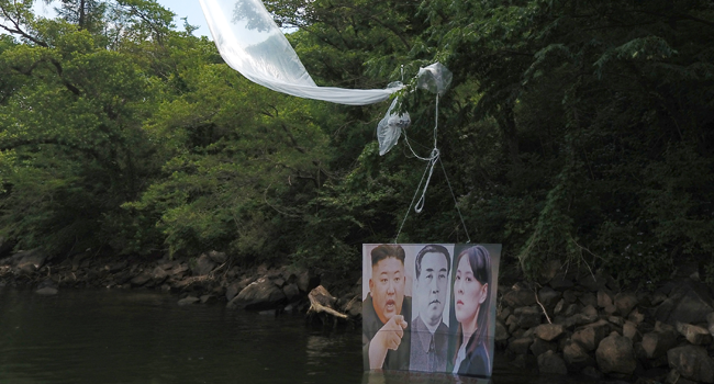 A balloon carrying a banner with portraits of North Korean leader Kim Jong Un (L), the late leader Kim Il Sung (C) and Kim Yo Jong, sister of Kim Jong Un, is caught on a tree after being launched by activists in Hongcheon on June 23, 2020. STR / YONHAP / AFP