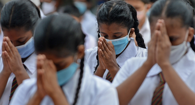 Students wearing facemasks gesture as they pray inside their school after it was reopened in Colombo on July 6, 2020.  LAKRUWAN WANNIARACHCHI / AFP
