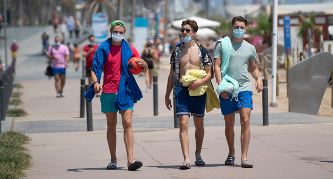People wear face masks as they walk along a beach in Barcelona, on July 18, 2020. Josep LAGO / AFP