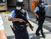 Armed police officers escort a van (behind) transporting Tong Ying-kit (not pictured) who is accused of deliberately driving his motorcycle into a group of police officers on July 1, as he arrives at West Kowloon court in Hong Kong on July 6, 2020. ISAAC LAWRENCE / AFP