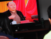 This file photo taken on December 20, 2011 shows Zheng Yanxiong, then-Communist Party Secretary of Shanwei prefecture, speaking on television as villagers watch the broadcast in Wukan, Guangdong province. MARK RALSTON / AFP