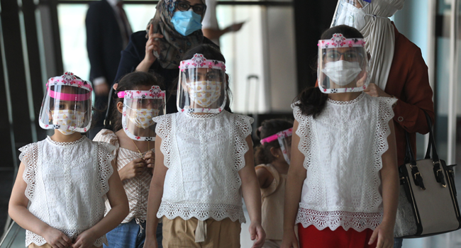 An Iraqi family wearing protective masks walk at the departure hall of Baghdad international airport following its reopening on July 23, 2020, after a closure forced by the coronavirus pandemic restrictions aimed at preventing the spread of the deadly COVID-19 illness in Iraq. AHMAD AL-RUBAYE / AFP