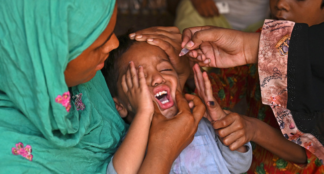 A health worker administers polio vaccine drops to a child during a polio vaccination door-to-door campaign in Lahore on August 16, 2020. Arif ALI / AFP