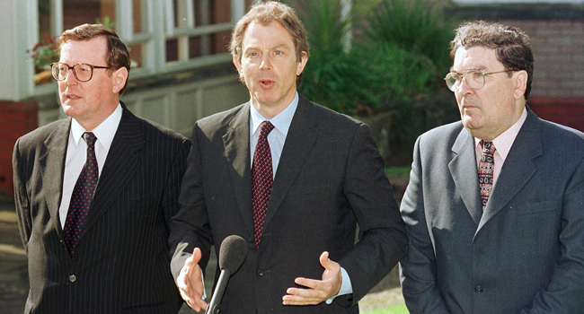 In this file photo taken on May 21, 1998 British Prime Minister Tony Blair (C) talks to the press after a meeting with and Ulster Unionist leader David Trimble (L) and SDLP leader John Hume to encourage a Yes vote for Friday's peace referendum. GERRY PENNY / AFP