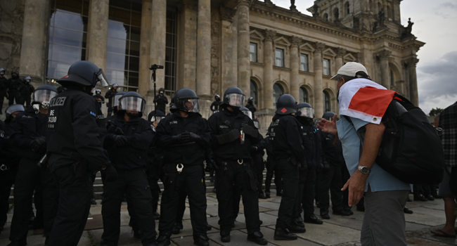 A man wrapped in a black-white-red flag leans towards the German riot policemen standing guard in front of the Reichstag building, which houses the Bundestag lower house of parliament, as protesters tried to storm in at the end of a demonstration called by far-right and COVID-19 deniers to protest against restrictions related to the new coronavirus pandemic, in Berlin, on August 29, 2020.  John MACDOUGALL / AFP