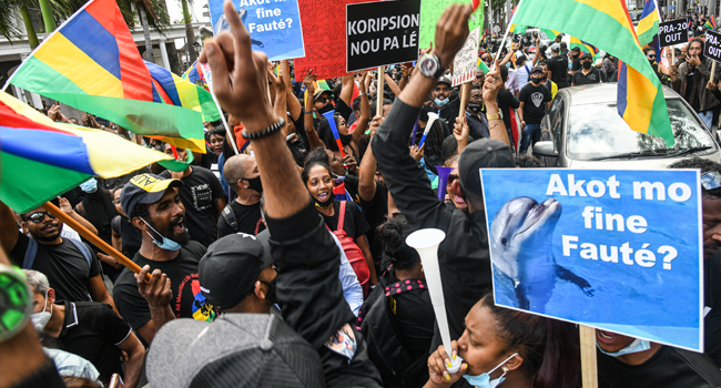 People hold up the national flag and placards as they protest against the government's response to the tanker oil spill disaster that happened in early August in Port Louis, on the island of Mauritius, on August 29, 2020. Fabien Dubessay / AFP