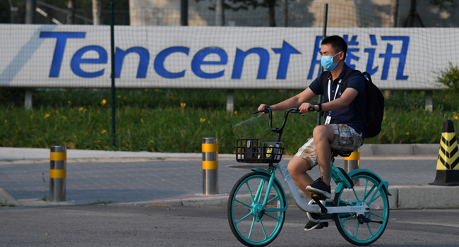A man walks past a sign for Tencent, the parent company of Chinese social media giant WeChat, outside the Tencent headquarters in Beijing on August 7, 2020. GREG BAKER / AFP