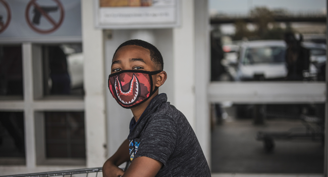 A boy wears a face mask as a preventive measure against the spred of the COVID-19 coronavirus as he queues outside Makro in Soweto, Johannesburg, on March 24, 2020. MARCO LONGARI / AFP