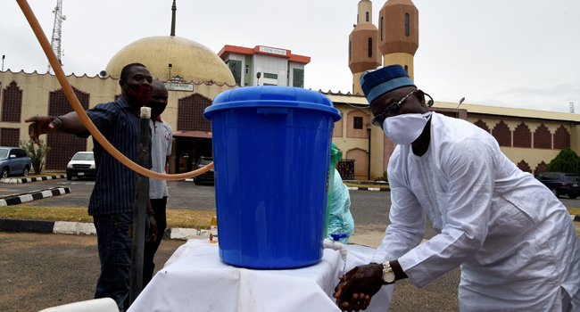 A man wash hands with sanitiser as he arrives at a Mosque following reopening of Mosques and lifting of restrictions on religious gatherings by the government as part of a set of measures taken to curtail the spread of COVID-19 Coronavirus at the Secretariat Community Central Mosque, Alausa in Lagos, on August 7, 2020. PIUS UTOMI EKPEI / AFP