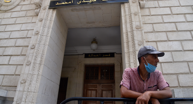 A man waits outside the Sidi Mohamed tribunal in the Algerian capital Algiers where the trial of detained journalist Khaled Drareni began, on August 3, 2020. RYAD KRAMDI / AFP