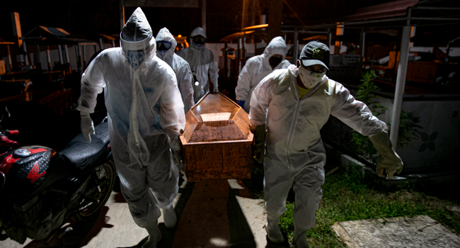In this file photo taken on May 30, 2020 gravediggers wearing protective clothing carry the coffin of a victim of the novel coronavirus COVID-19 for its burial at the Recanto da Paz Municipal Cemetery in the city of Breves, southwest of Marajo Island, an island at the mouth of the Amazon River in the Brazilian state of Para,Brazil. Tarso SARRAF / AFP