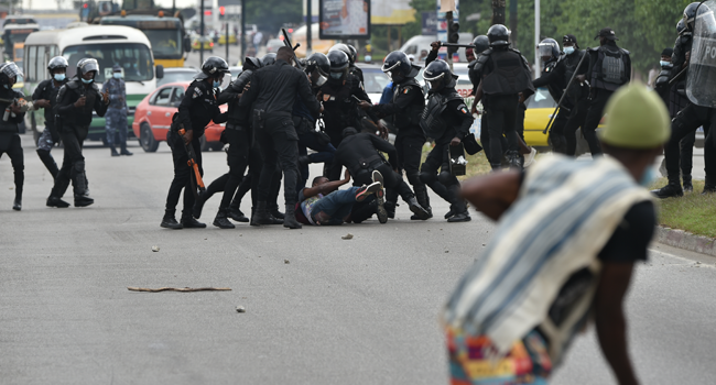Policemen beat a demonstrator during a rally of former Ivory Coast President Laurent Gbagbo's supporters to protest against his absence on the presidential candidates electoral list, near the electoral commission headquarters on boulevard Latrille in Cocody district of Abidjan on August 6, 2020. SIA KAMBOU / AFP
