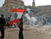 A Lebanese protester waves the national flag during clashes with security forces in downtown Beirut on August 8, 2020, following a demonstration against a political leadership they blame for a monster explosion that killed more than 150 people and disfigured the capital Beirut. JOSEPH EID / AFP