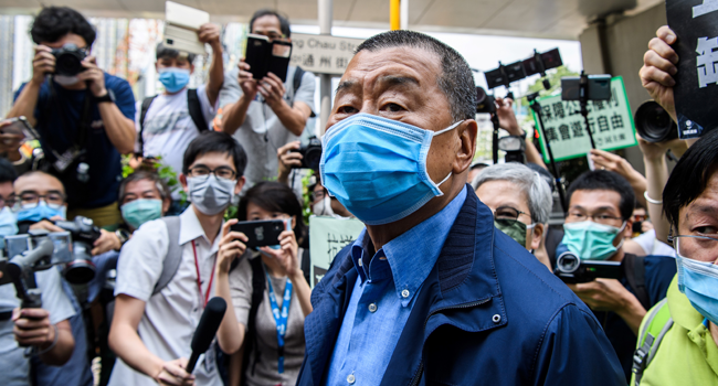 In this file photo taken on May 18, 2020, Hong Kong media tycoon and founder of the Apple Daily newspaper Jimmy Lai (C) arrives at the West Kowloon Magistrates Court for charges related to last year's protests in Hong Kong. Anthony WALLACE / AFP