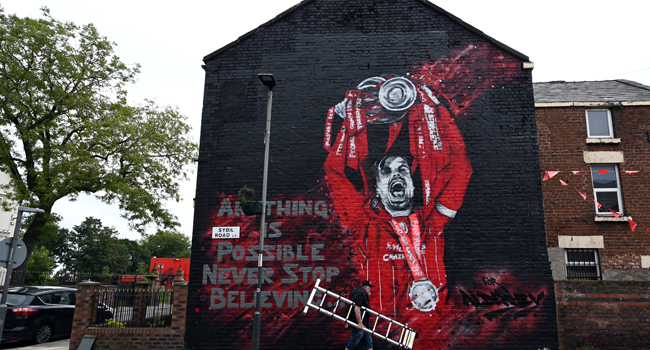 The finished new mural of Liverpool's English midfielder Jordan Henderson lifting the Premier League trophy created by graffiti artists MurWalls in collaboration with The Redmen TV, independent Liverpool FC media, is seen on the side of a house outside Anfield stadium in Liverpool, northwest England, on July 25, 2020. Paul ELLIS / AFP