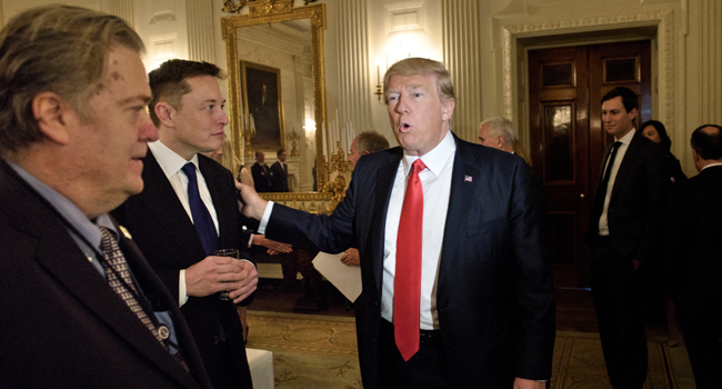 In this file photo former Trump advisor Steve Bannon (L) watches as US President Donald Trump greets Elon Musk, SpaceX and Tesla CEO, before a policy and strategy forum with executives in the State Dining Room of the White House February 3, 2017 in Washington, DC. Brendan Smialowski / AFP