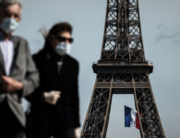 In this file photo taken on May 11, 2020, a man and a woman wearing face masks walk on Trocadero Plaza as a French national flag flies on the Eiffel Tower in background in Paris on the first day of France's easing of lockdown measures in place for 55 days to curb the spread of the COVID-19 pandemic, caused by the novel coronavirus. PHILIPPE LOPEZ / AFP