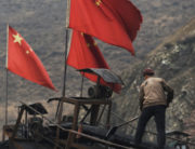 (FILES) This file photo taken on November 20, 2015 shows Chinese flags next to a worker clearing a conveyer belt used to transport coal, near a coal mine at Datong, in China's northern Shanxi province.