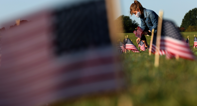 Carmen Wilke places flags at a COVID Memorial Project install of 20,000 American flags on the National Mall as the United States crosses the 200,000 lives lost in the COVID-19 pandemic September 22, 2020 in Washington, DC. Win McNamee/Getty Images/AFP