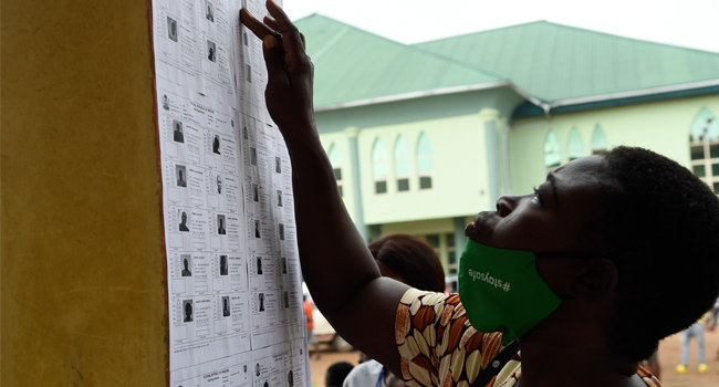 A woman looks at election lists pasted on a wall up to vote during the Edo State governorship elections in Benin City, Midwestern Nigeria, on September 19, 2020. PIUS UTOMI EKPEI / AFP