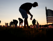 Volunteers with the COVID Memorial Project install 20,000 American flags on the National Mall as the United States crosses the 200,000 lives lost in the COVID-19 pandemic September 20, 2020 in Washington, DC. McNamee/Getty Images/AFP