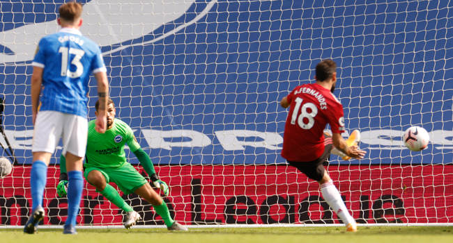 Manchester United's Portuguese midfielder Bruno Fernandes (R) takes a penalty and scores his team's third goal during the English Premier League football match between Brighton and Hove Albion and Manchester United at the American Express Community Stadium in Brighton, southern England on September 26, 2020. JOHN SIBLEY / POOL / AFP