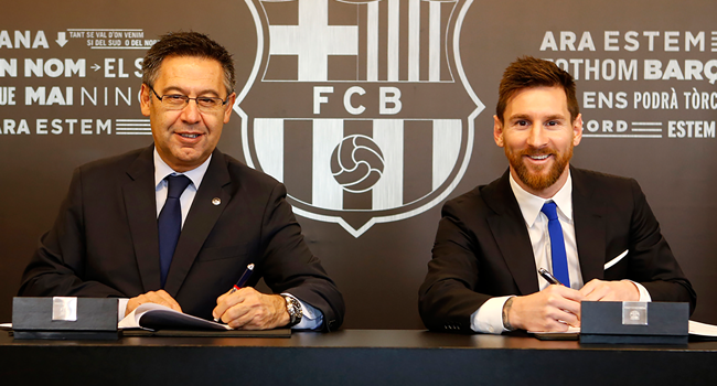 In this file handout photo taken on November 25, 2017 in Barcelona and released by the Barcelona FC press office, Barcelona FC President Josep Maria Bartomeu (L) and Barcelona's Argentinian forward Lionel Messi sign a contract extension keeping Messi at Barcelona until 2021.  Handout / FC BARCELONA / AFP