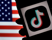 In this file photo illustration taken on August 03, 2020, the social media application logo, TikTok is displayed on the screen of an iPhone on an US flag as the background in Arlington, Virginia. Olivier DOULIERY / AFP