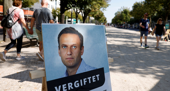 """A poster with a picture of Russian opposition leader Alexei Navalny with the headline """"poisoned"""" is seen outside the Russian embassy on Unter den Linden in Berlin during an anti-government protest on September 23, 2020. Odd ANDERSEN / AFP"""
