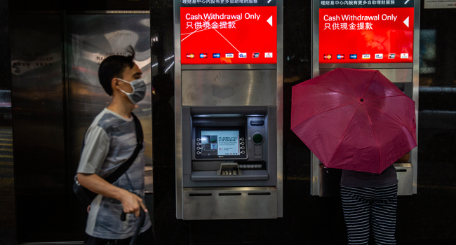 A women (R) uses a HSBC automated teller machine (ATM) in Hong Kong on September 21, 2020. ISAAC LAWRENCE / AFP
