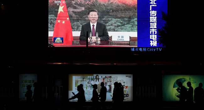 An image of Chinese President Xi Jinping appearing by video link at the United Nations 75th anniversary is seen on an outdoor screen as pedestrians walk past below in Beijing on September 22, 2020. GREG BAKER / AFP