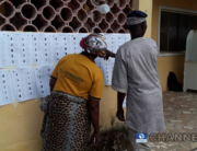 Voters in Ondo state inspect a notice board at a polling unit.