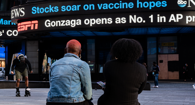 """An electronic billboard in Times Square announces """"stocks soar on vaccine hopes"""" on November 9, 2020 in New York City. David Dee Delgado/Getty Images/AFP"""