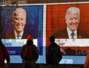 People watch a big screen displaying the live election results in Florida at Black Lives Matter plaza across from the White House on election day in Washington, DC on November 3, 2020. Olivier DOULIERY / AFP