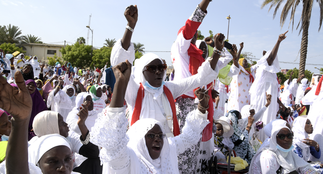 Women hold their fist in the air during a protest against French President at the Place de l'obelisque, in Dakar, on November 7, 2020.