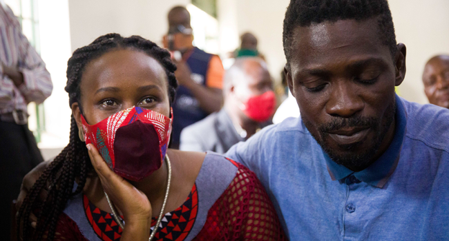 Ugandan musician turned politician Robert Kyagulanyi (R), also known as Bobi Wine, appears at the court with his wife Barbara Itungo, in Iganga, on November 19, 2020. Badru KATUMBA / AFP