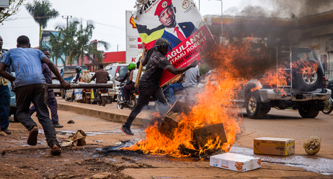 A supporter of Ugandan musician turned politician Robert Kyagulanyi, also known as Bobi Wine, carries his poster as they protest on a street against the arrest of Kyagulanyi during his presidential rally in Kampala, Uganda, on November 18, 2020.  Badru KATUMBA / AFP