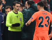 Romanian referee Ovidiu Hategan (in yellow) talks to Istanbul Basaksehir's staff members past Istanbul Basaksehir's French forward Demba Ba (2ndR) after the game was suspended amid allegations of racism by one of the match officials during the UEFA Champions League group H football match between Paris Saint-Germain (PSG) and Istanbul Basaksehir FK at the Parc des Princes stadium in Paris, on December 8, 2020. FRANCK FIFE / AFP