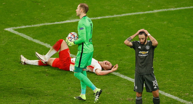 Manchester United's Portuguese midfielder Bruno Fernandes (R) reacts next to Leipzig's Hungarian goalkeeper Peter Gulacsi holding the ball as Leipzig's Hungarian defender Willi Orban lays on the ground during the UEFA Champions League Group H football match RB Leipzig v Manchester United in Leipzig, eastern Germany, on December 8, 2020. Odd ANDERSEN / AFP / POOL
