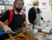 Volunteers prepare food packages to be distributed to people in need at the Zaqueo Association in Palma de Mallorca on December 2, 2020. JAIME REINA / AFP