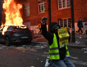 "A ""Yellow Vest"" (Gilet Jaune) anti-government protestor kneels raising his fist as he poses with a sign reading 'Living, Yes! Surviving, No!' near burning cars during a demonstration for 'social rights' and against the 'global security' draft law, which Article 24 would criminalise the publication of images of on-duty police officers with the intent of harming their 'physical or psychological integrity', in Paris, on December 5, 2020. Anne-Christine POUJOULAT / AFP"